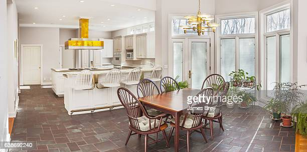 Spacious casual breakfast nook adjoining modern white kitchen