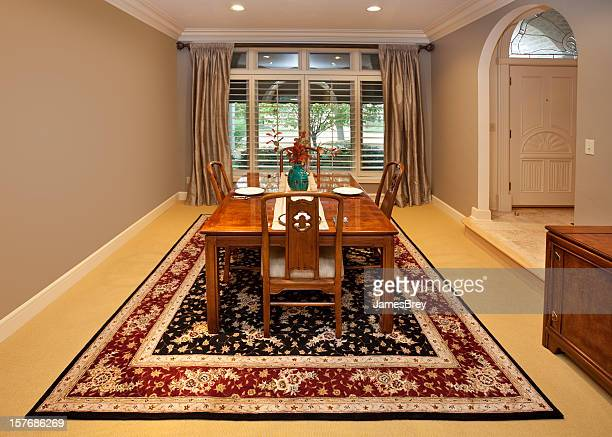 spacious dining room with table set for four - persian rug stock photos and pictures