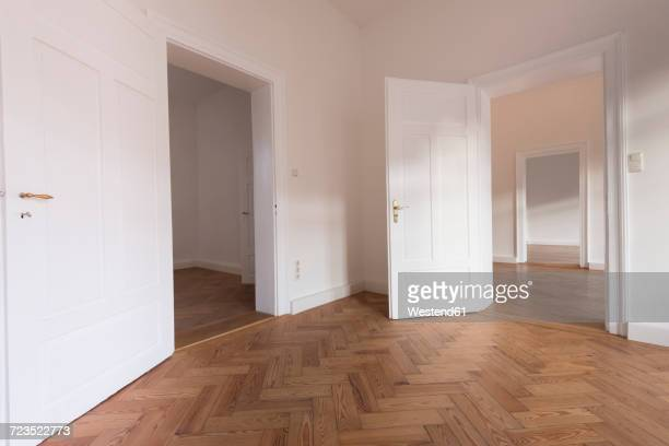 spacious empty flat with herringbone parquet - tür stock-fotos und bilder