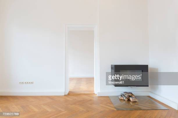 Spacious empty living room with herringbone parquet and fireplace