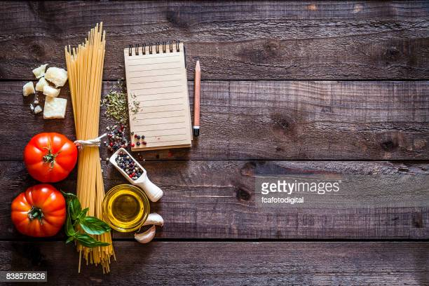 Spagetti, ingredients and cookbook on rustic wooden table
