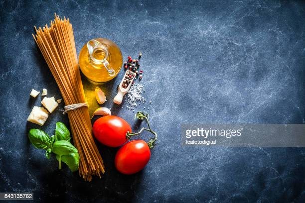Spagetti with ingredients on dark table
