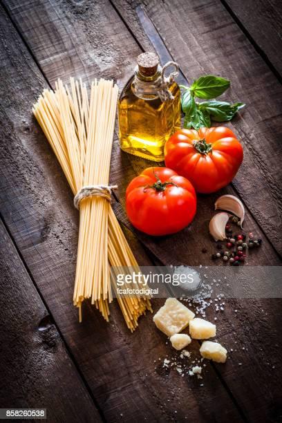 Spagetti con ingredientes en la mesa de madera rústica