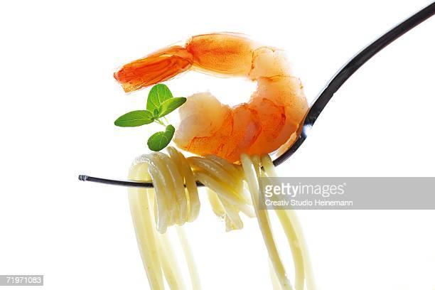 Spaghetti and prawn on fork, close-up