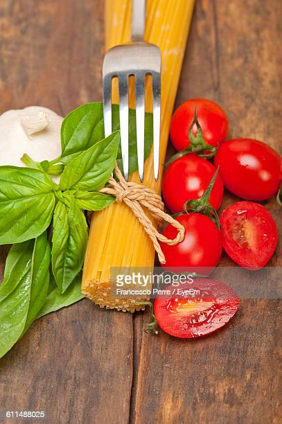 Spaghetti And Tomatoes By Basil And Garlic On Wooden Table