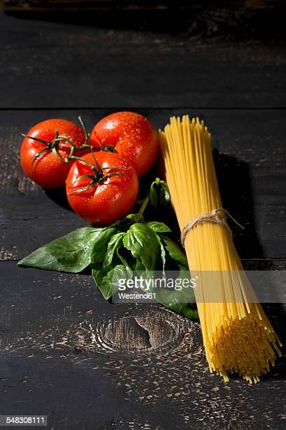 Spaghetti, basil and tomatoes on dark wood