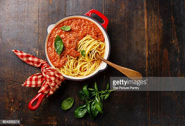 Spaghetti Bolognese with tomato sauce and basil in iron pan on wooden background