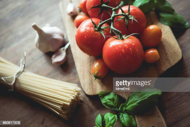 Spaghetti, garlic, basil and tomatoes on a cutting board