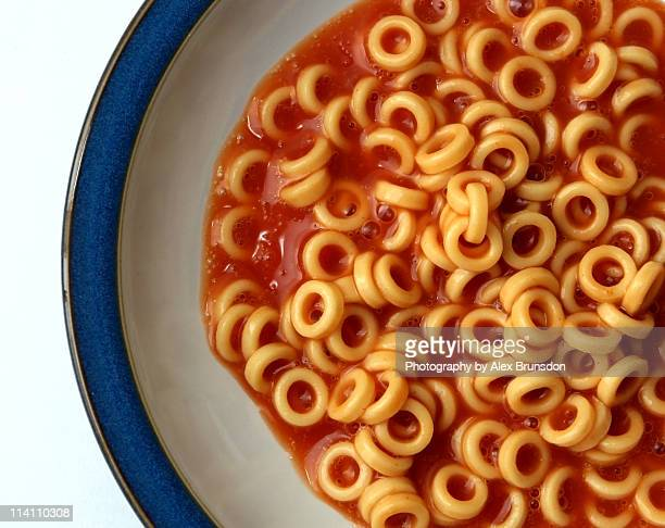 spaghetti hoops on white plate with blue border - spaghetti stock pictures, royalty-free photos & images