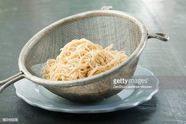 Spaghetti in metal colander resting on plate