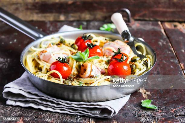 spaghetti pasta with roasted cherry tomatoes, bacon slices, capers and herbs in a pan ready to serve, selective focus - course meal stockfoto's en -beelden