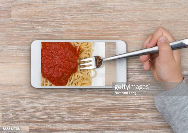 Spaghetti taken from mobile phone screen with fork