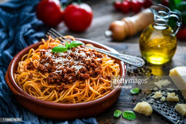 spaghetti with bolognese sauce shot on rustic wooden table - bolognese sauce stock pictures, royalty-free photos & images