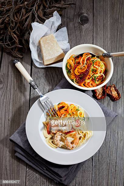 Spaghetti with scampis and vegetables on plate, bowl with spirals of tomato and zucchini, dried tomato