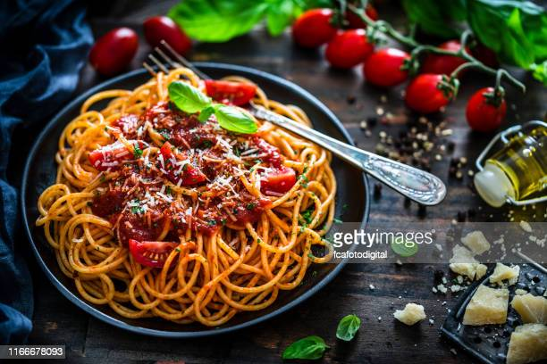 spaghetti with tomato sauce shot on rustic wooden table - sauce stock pictures, royalty-free photos & images