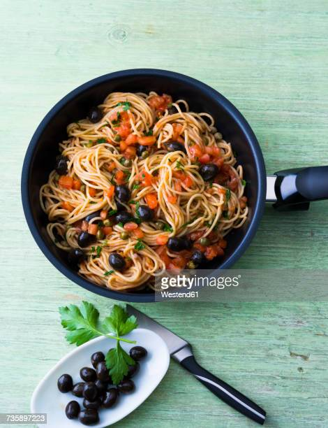 Spaghetti with tomatoes, olives and capers in a pan
