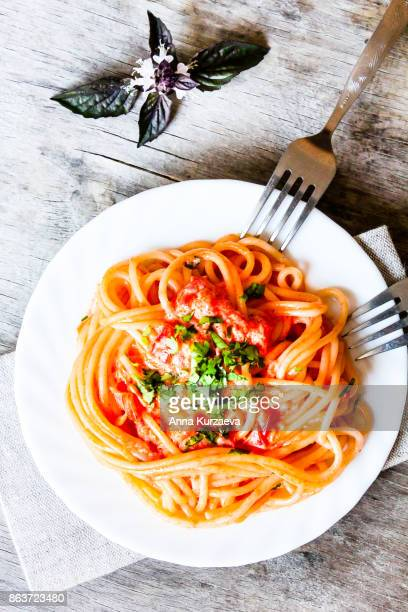 Spaghetti with vodka sauce topped with freshly grated parmesan cheese and fresh parsley on a plate, directly above view