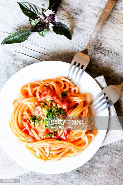 Spaghetti with vodka sauce topped with freshly grated parmesan cheese and fresh parsley on a plate, selective focus