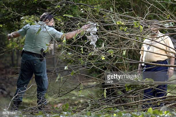 A member of the Guardia Civil collects evidence from the site of an ETA bomb blast near Zaragoza 27 September 2005 The explosion happened near an...