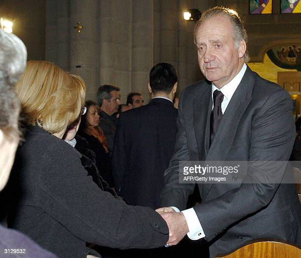 A visibly moved King Juan Carlos shakes the hand of a relative of one of the victims of the March 11 Madrid bomb attacks at the memorial service for...