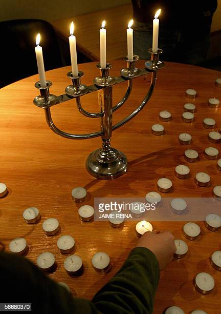 A woman lights a candle during a ceremony in Palma de Mallorca's synagogue 26 January 2006 on the eve of Holocaust memorial day The UN General...