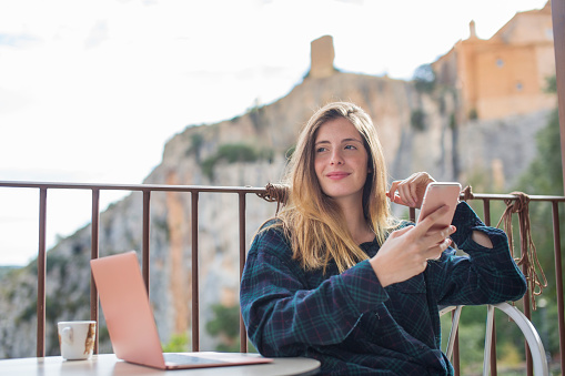 Spain, Alquezar, portrait of relaxed young woman with laptop and cell phone sitting on terrace - gettyimageskorea
