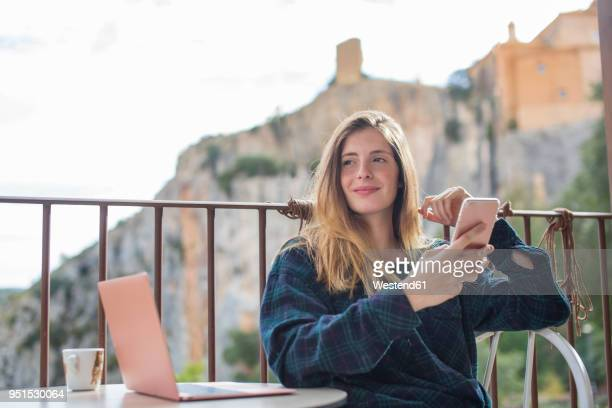 Spain, Alquezar, portrait of relaxed young woman with laptop and cell phone sitting on terrace