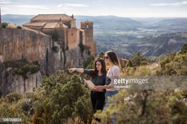 spain, alquezar, two young women with map on a hiking trip - aragon fotografías e imágenes de stock