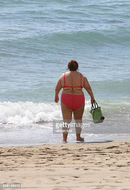 Spain Andalucia Nerja Corpulent woman wearing a bikini at the beach