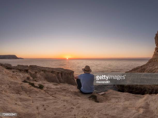 spain, andalusia, cabo de gata, back view of man looking at the sea at sunrise - look back at early colour photography stock photos and pictures
