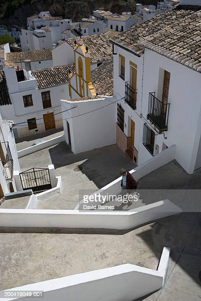spain, andalusia, cadiz province, setenil, man walking down footpath - setenil de las bodegas stock-fotos und bilder
