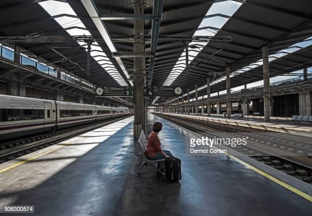 spain, andalusia, cordoba, woman on empty train platform - plataforma de estação de trem - fotografias e filmes do acervo