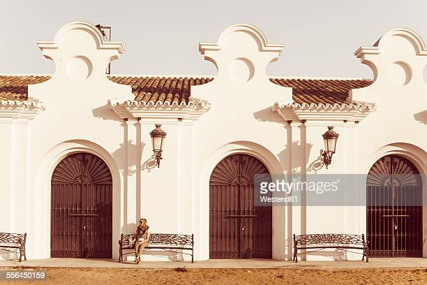 Spain, Andalusia, El Rocio, female tourist sitting in front of Ermita del Rocio