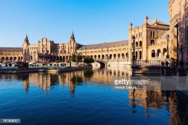 Spain, Andalusia, Seville, Plaza de Espana reflecting in water surface
