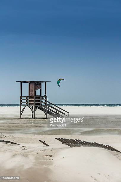 Spain, Andalusia, Tarifa, Beach and attendants tower, kitsurfer in the background