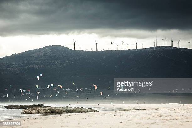 Spain, Andalusia, Tarifa, Kiter in front of mountain with wind wheels