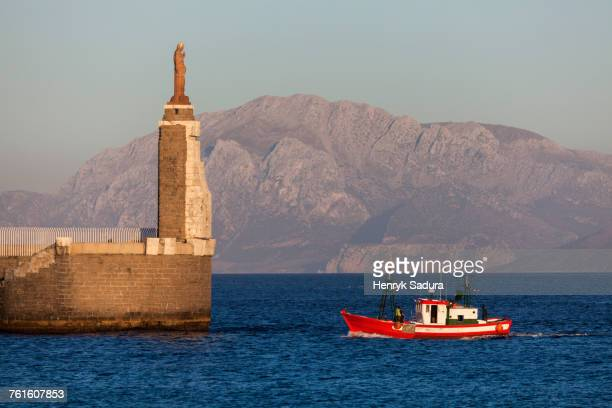 spain, andalusia, tarifa, port of tarifa, jesus christ statue by sea and red fishing boat - tarifa stock pictures, royalty-free photos & images