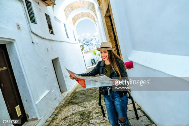 spain, andalusia, vejer de la frontera, happy young woman holding map in the alley el callejon de las monjas - callejon stock pictures, royalty-free photos & images