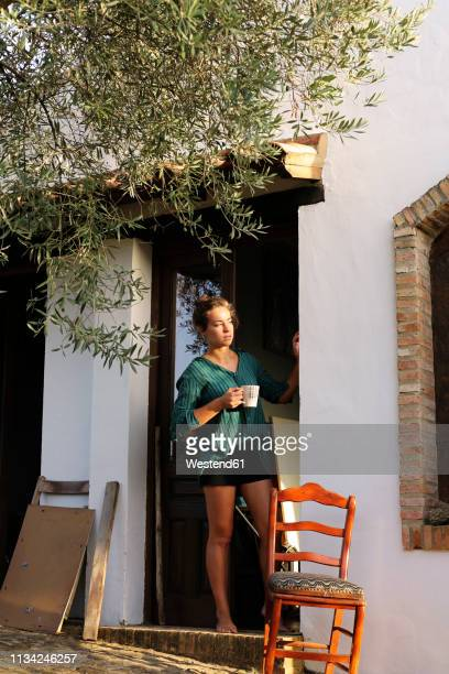 spain, andalusia, young woman with cup uf coffee standing barefoot at house entrance looking at distance - andalucia fotografías e imágenes de stock