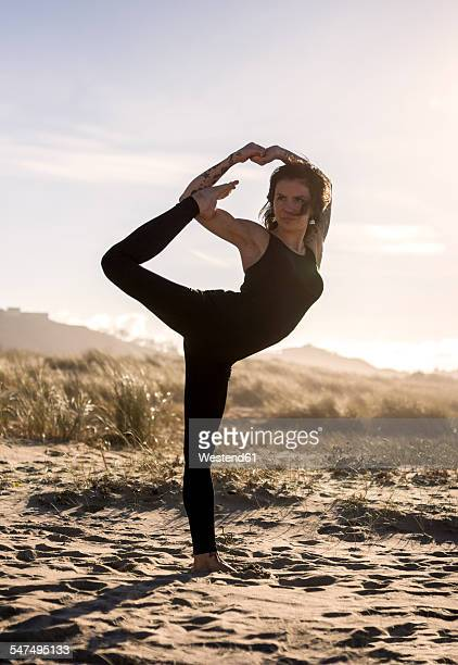 spain, asturias, aviles, woman practicing yoga on the beach - standing on one leg stock pictures, royalty-free photos & images