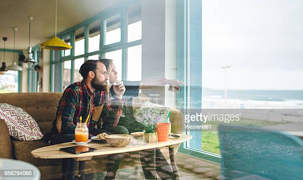 Spain, Asturias, Couple enjoying the seascape through the cafe window while having a brunch