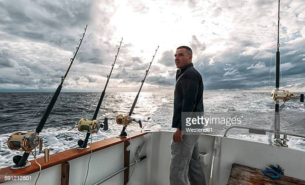 Spain, Asturias, Fisherman on fishing boat on Cantabrian Sea