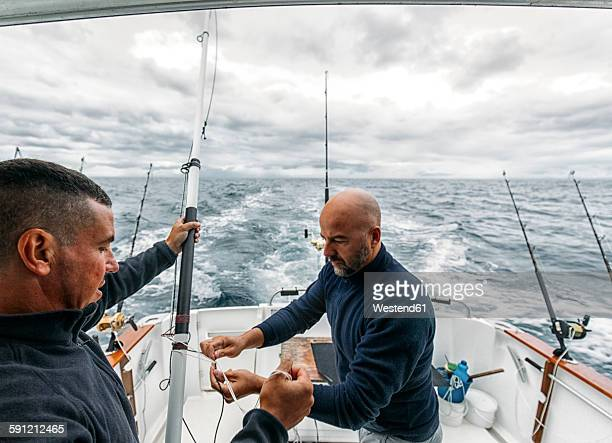 Spain, Asturias, Fishermen on fishing boat on Cantabrian Sea