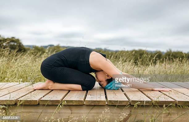 spain, asturias, gijon, woman doing yoga outdoors - childs pose stock photos and pictures