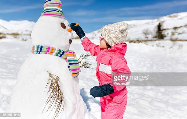 Spain, Asturias, Girl building a snowmen in winter
