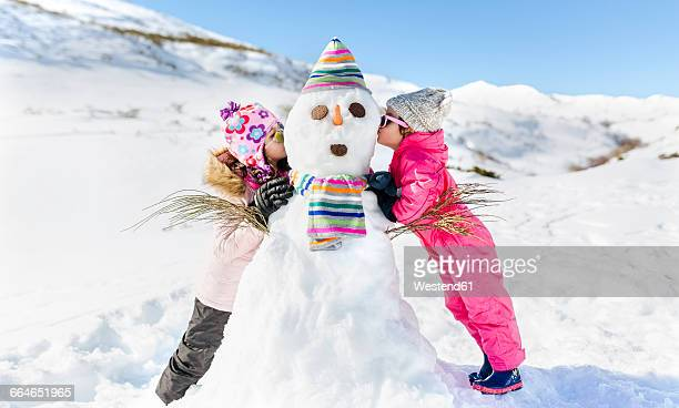 spain, asturias, kids playing with snowmen, kissing - ski wear stock pictures, royalty-free photos & images