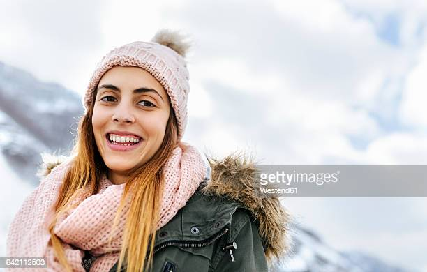 Spain, Asturias, portrait of happy young woman in the snowy mountains