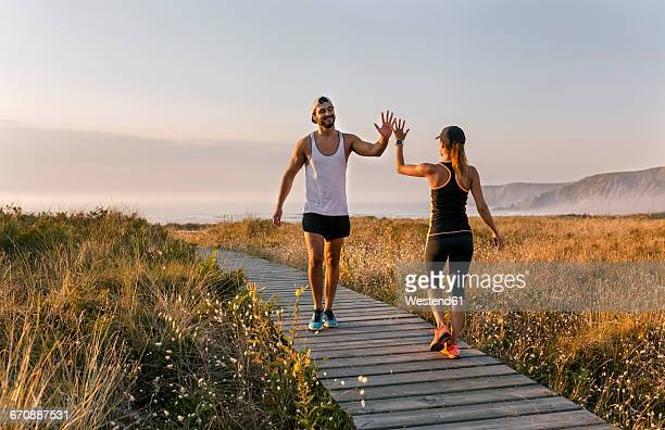 Spain, Aviles, athletes couple hitting five on the beach in the evening