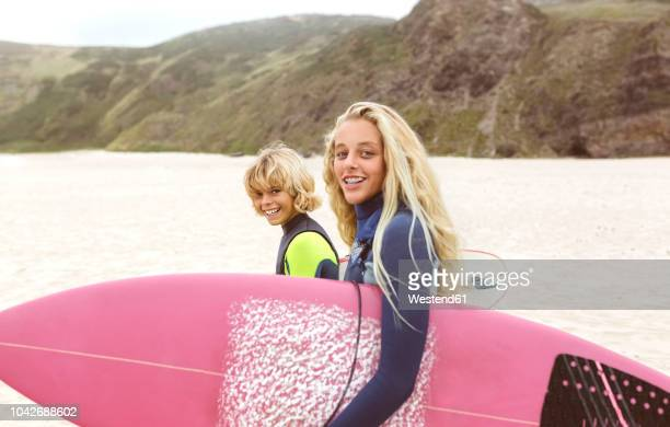 spain, aviles, portrait of two smiling young surfers on the beach - asturien stock-fotos und bilder