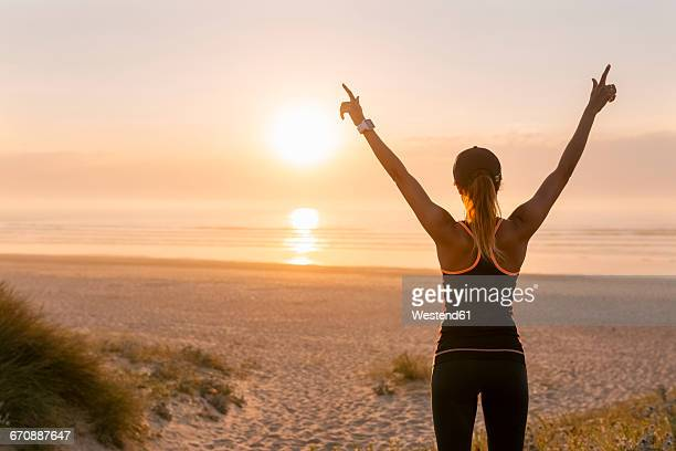 Spain, Aviles, young athlete woman enjoying the sunset on the beach